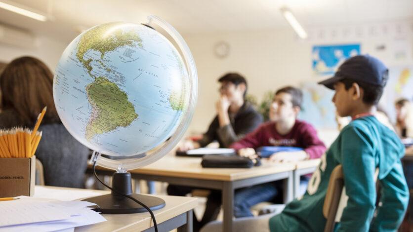 Elever runt ett bord i klassrummet, en jordglob står i förgrunden