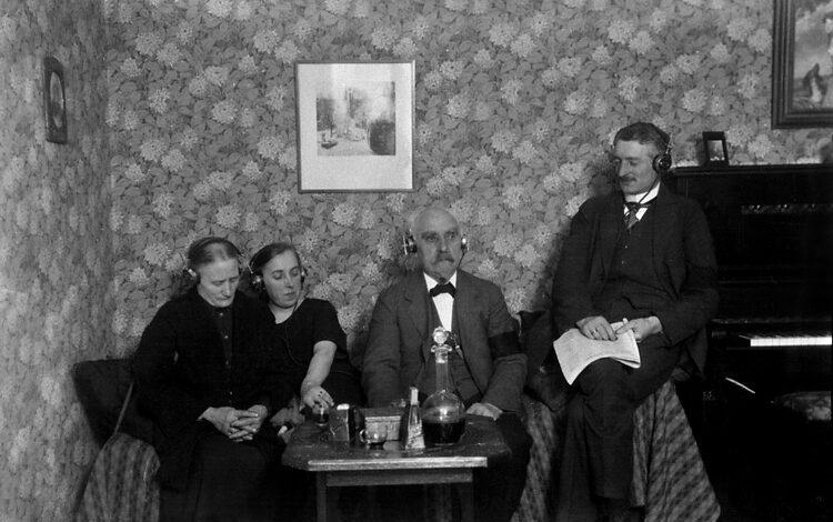 Äldre bild med fyra personer som lyssnar op en radioutsändning